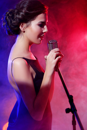 Young beautiful woman singing in colourful smoke, close up Stock Photo