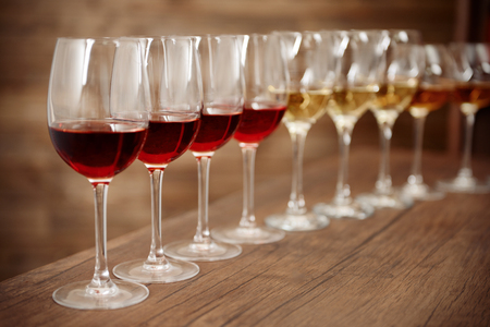 Many glasses of different wine in a row on bar counter Stock Photo