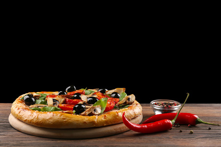 Delicious tasty pizza with ingredients on wooden table Stock Photo