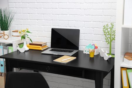 Stijlvolle werkplek met laptop in huis Stockfoto