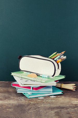 Federmäppchen mit verschiedenen Schreibwaren auf altem Holztisch, auf Tafelhintergrund Standard-Bild