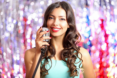 Portrait of beautiful singing woman against bright glitter background 写真素材