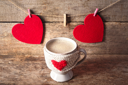Coffee cup with milk and two hearts on wooden background closeup