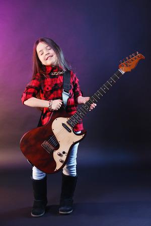 Little rock star playing guitar on dark purple background