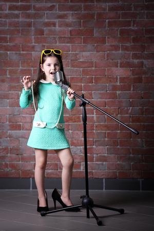 """Hermosa niña vestida y """"TACONES DE LA MADRE"""" con micrófono sobre fondo de pared de ladrillo"""