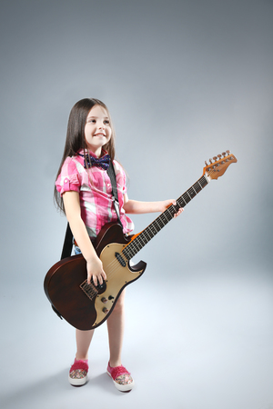 Beautiful artistic little girl playing guitar on grey background