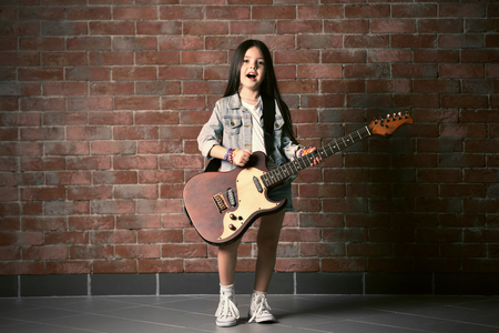 Beautiful little girl with guitar on brick wall background