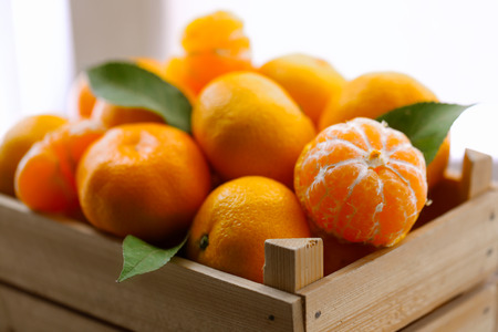 Tangerines in wooden crate, on old wooden table, close up Stockfoto
