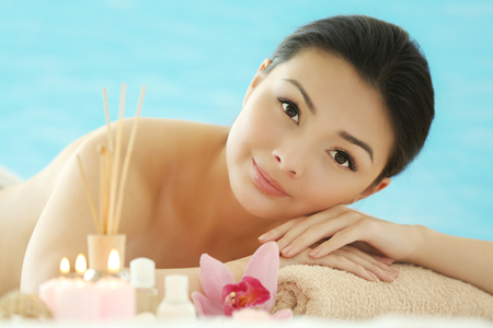 Spa concept. Young pretty woman relaxing on blue background, close up