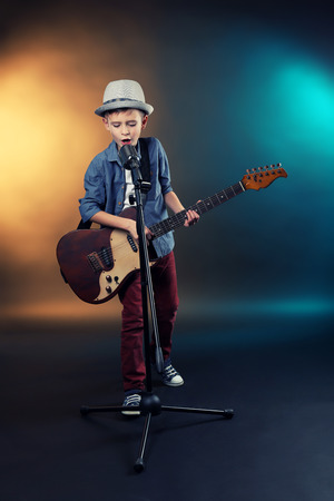 Little boy playing guitar and singing with microphone on a dark lighted background Stock Photo