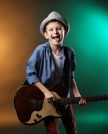 Little boy playing guitar on a dark lighted background