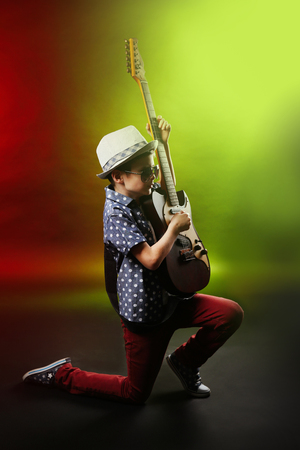 Little boy playing guitar on a bright background Stock Photo