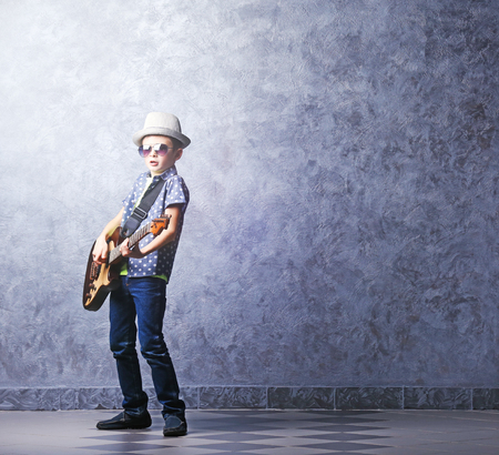 Little boy playing guitar on a grey wall background Stock Photo