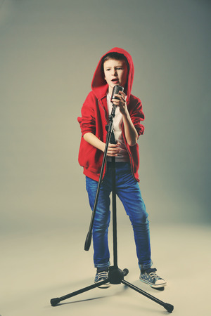 Little boy singing with microphone on a grey background Stok Fotoğraf