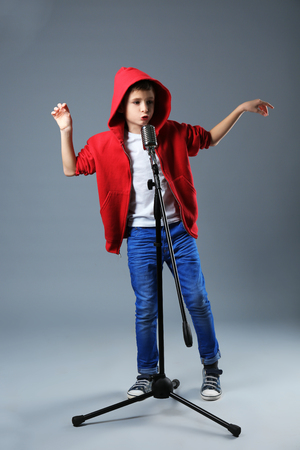 Little boy singing with microphone on a grey background Stock Photo