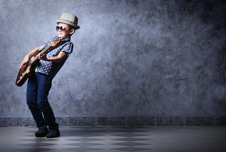 Little Boy a suonare la chitarra su un muro grigio Sfondo
