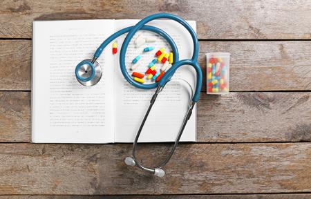 Estetoscopio con pastillas y libro sobre mesa de madera