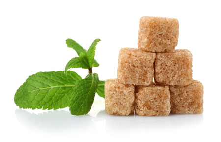 Pile of brown sugar cubes and stevia isolated on white background Stock Photo