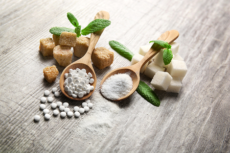 Pile of brown sugar cubes and stevia  on grey wooden background Stock Photo