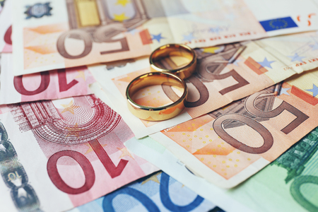 Golden wedding rings on euro banknotes background. Marriage of convenience Stock Photo