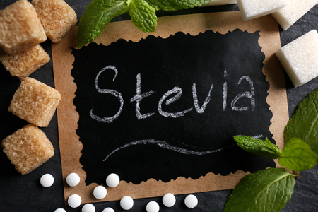 Word STEVIA in sugar frame on black background, close up Stock Photo