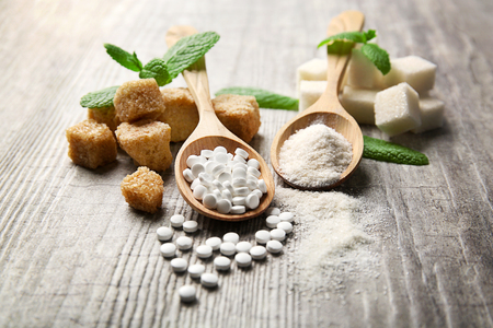 Pile of brown sugar cubes and stevia  on grey wooden background Stok Fotoğraf