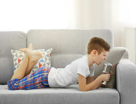 Little boy singing with a microphone on a sofa at home