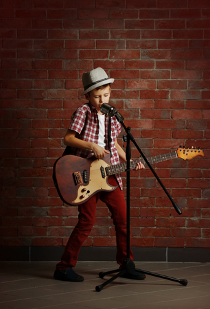 Little boy playing guitar and singing with microphone on a brick wall background Stok Fotoğraf