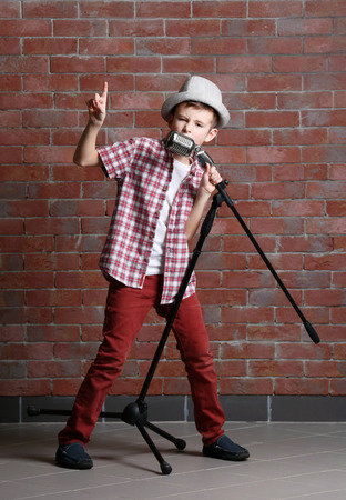 Little boy singing with microphone on a brick wall background
