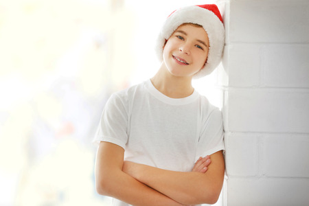 Portrait of boy in Christmas red hat near white brick wall