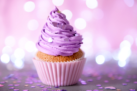 Cupcake with purple cream icing on a glitter background, close up Stock Photo