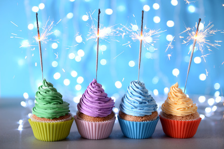 Varicolored cupcakes icing with sparklers in a row on a glitter background Stok Fotoğraf