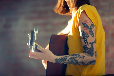 Woman with tattoo playing guitar on brick background