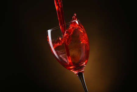 Wine pouring in glass on brown background Reklamní fotografie