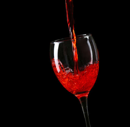 Wine pouring in glass on black background Stock Photo