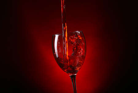 Wine pouring in glass on dark red background