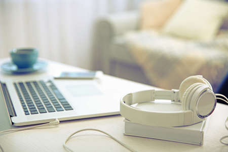 Headphones, book and laptop on white table against defocused background
