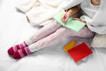 Woman in pajamas writing diary on her bed
