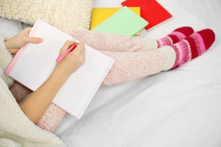 Woman in pajamas writing diary on her bed Banco de Imagens - 104675735
