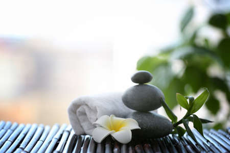 Spa stones with towel and tropical flower on blurred background