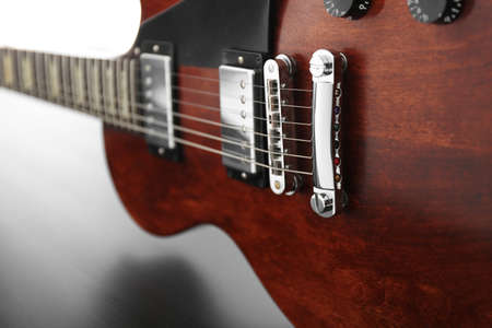 Brown electric guitar on black wooden background, close up