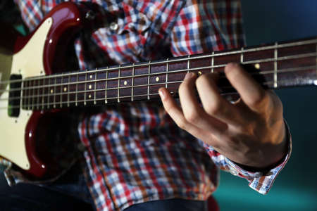 Young man playing electric guitar on lighted dark background Banque d'images