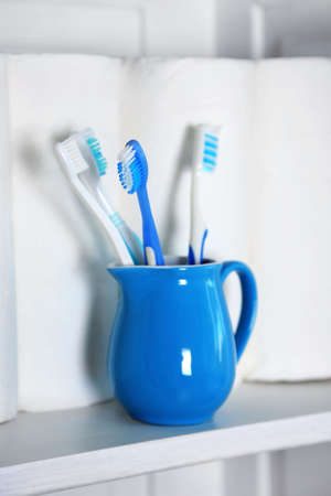 Bathroom set with toothbrushes and paper towels on a shelf in light interior