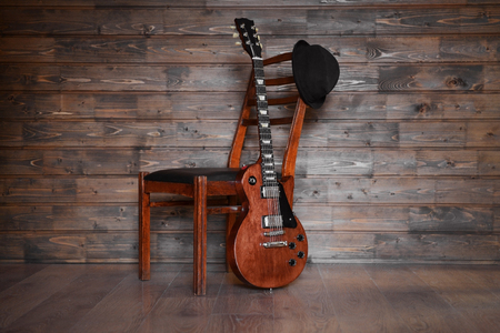 Brown electric guitar with chair and black hat on wooden background, close up