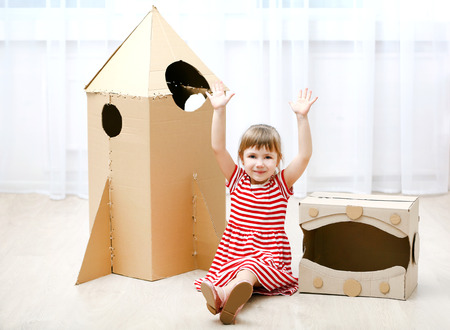 Little cute girl playing with cardboard space rocket and astronaut helmet in room Stock Photo