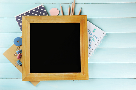 Small school blackboard with stationery on wooden background