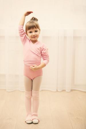 Little cute girl in pink leotard making new ballet movement at dance studio Standard-Bild - 107461769
