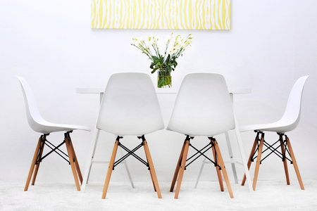 Moderne eetkamer. Witte stoelen en tafel met boeket bloemen, abstracte afbeelding aan de muur Stockfoto