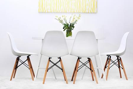 Salle à manger moderne. Chaises blanches et table avec bouquet de fleurs, photo abstraite sur le mur Banque d'images