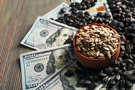 Dollar banknotes and sunflower seeds on wooden background. Agricultural income concept
